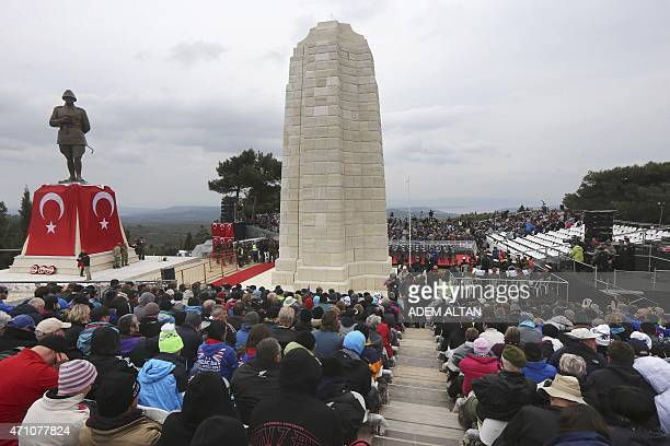 People attend a memorial service, on April 25 in front of the Ataturk Memorial , draped with the Turkish flag, and the New Zealand Memorial on Chunuk...