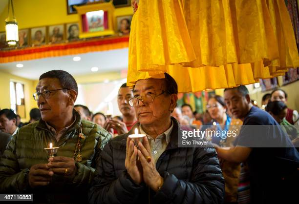 People attend a prayer service at the United Sherpa Association monastery April 27 2014 in the Elmhurst neighborhood of the Queens borough of New...