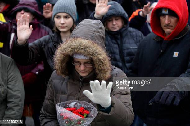 People attend a prayer vigil as they holds their hands up outside Henry Pratt Company on February 17 2019 in Aurora Illinois Six people including a...