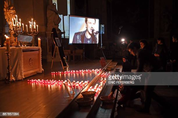 People attend a prayer vigil in memory of late French rock star Johnny Hallyday at the SaintRoch Church in Paris on December 7 2017 French music icon...