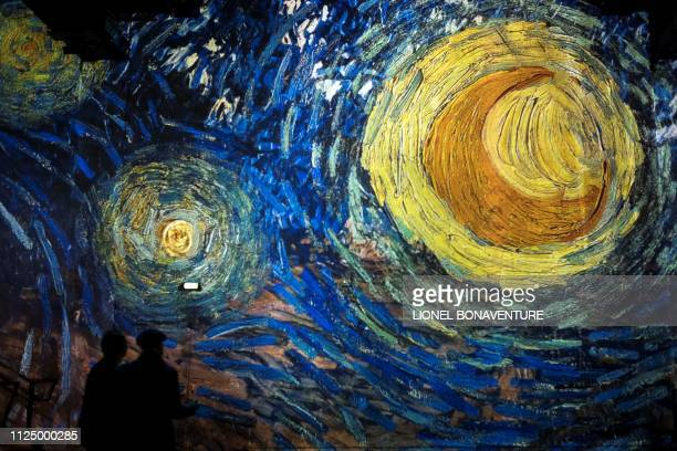 TOPSHOT People attend a press visit of the immersive exhibition Nuit Etoilée devoted to painter Vincent Van Gogh by multimedia artist Gianfranco...