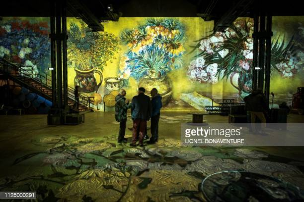 People attend a press visit of the immersive exhibition Nuit Etoilée devoted to painter Vincent Van Gogh by multimedia artist Gianfranco Iannuzzi on...