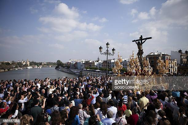 People attend a procession of El Cachorro brotherhood during Holy Week celebrations in Sevilla on April 18 2014 Christian believers around the world...