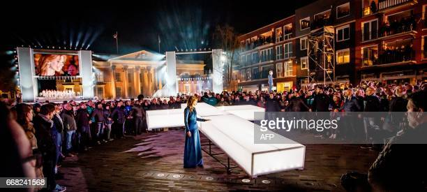 People attend a procession with the white cross of the TV broadcast The Passion through the streets of Leeuwarden on April 13 2017 It is the seventh...