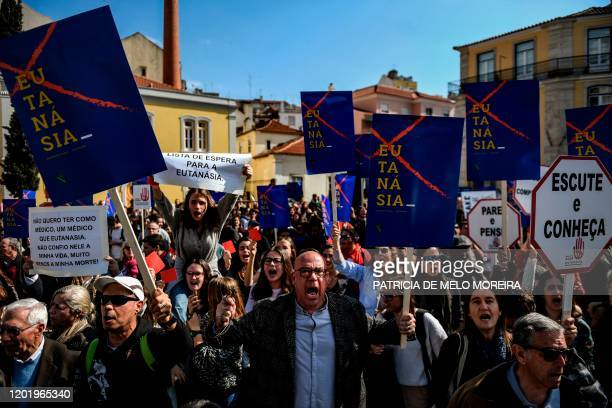 People attend a protest against the decriminalization of euthanasia in front of the parliament on February 20, 2020 in Lisbon as lawmakers debate...