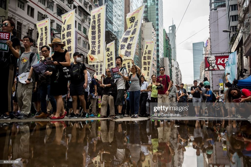 TOPSHOT - People attend a protest march in Hong Kong on July 1, 2017, coinciding with the 20th anniversary of the city's handover from British to Chinese rule. China's President Xi Jinping warned July 1 that any challenge to Beijing's control over Hong Kong crossed a 'red line', as thousands calling for more democracy marched through the city 20 years since it was handed back by Britain. / AFP PHOTO / Isaac LAWRENCE