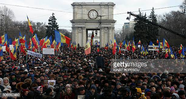People attend a rally in front of the Parliament building in Chisinau on January 24 2016 Some 40000 opposition demonstrators took to the streets of...