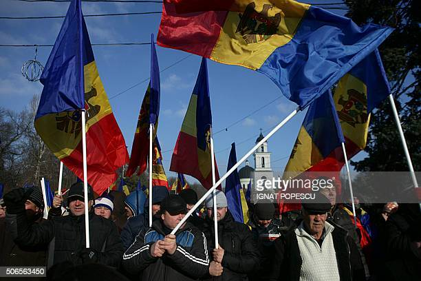 People attend a rally in front of the Parliament building in Chisinau on January 24, 2016. Some 40,000 opposition demonstrators took to the streets...