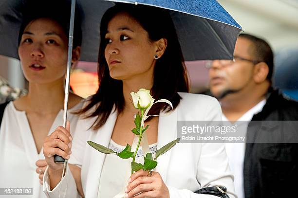 People attend a silent march for Jenny Loh and Fan Piopo the owners of the Asian Glories restaurant and Jenny's mother who were killed in the downed...
