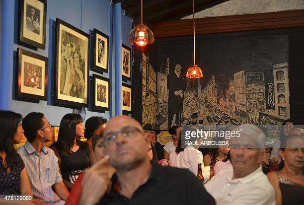People attend a tribute to tango singer and composer Carlos Gardel at the Casa Gardeliana Museum in Medellin Antioquia department Colombia on June 22...
