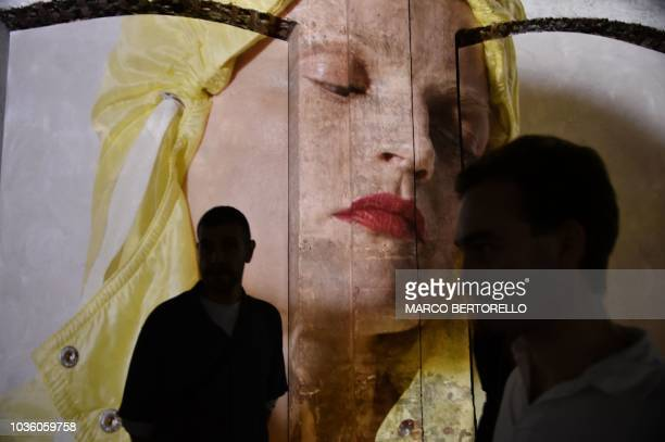 People attend a video presentation of creations by Moncler fashion house during the Women's Spring/Summer 2019 fashion shows in Milan on September 19...