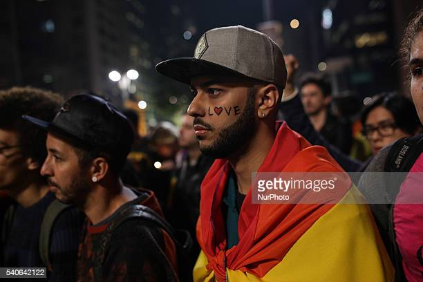 People attend a vigil in memory of victims of the mass shooting at the Pulse gay night club in Orlando in Sao Paulo Brazil on June 16 2016