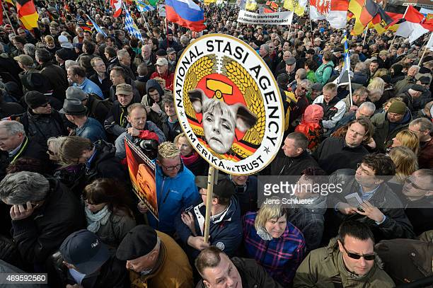 People attend a weekly Pegida demonstration on April 13 2015 in Dresden Germany A large number of supporters and opponents are expected to attend the...