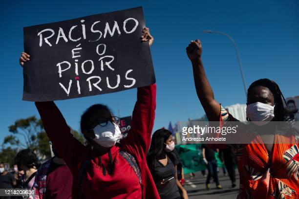 People attend an antiracist protest condemning the government of President Jair Bolsonaro amidst the coronavirus pandemic at the Esplanada dos...