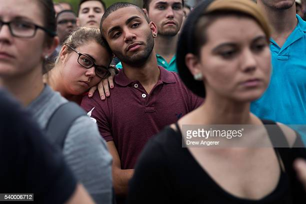 People attend an evening memorial service for the victims of the Pulse Nightclub shootings at the Dr Phillips Center for the Performing Arts June 13...