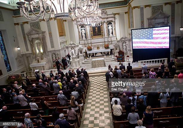 People attend an interfaith remembrance service at St Peter's Roman Catholic Church September 11 2014 in New York CIty This year marks the 13th...