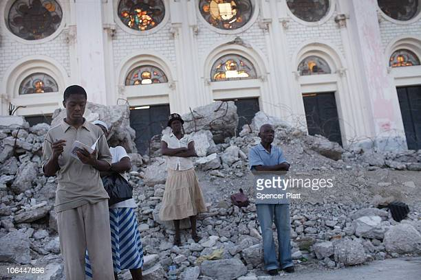People attend services for All Souls' Day on the rubble of the Cathedral of Our Lady of the Assumption church which was destroyed in the January 12...