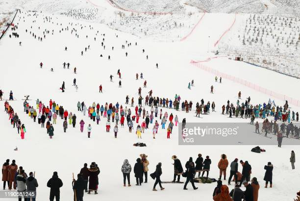 People attend the 14th Xinjiang Winter Tourism Trade Fair at a ski resort on Jiangjun Mountain on November 27 2019 in Altay Xinjiang Uyghur...