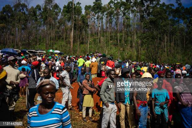 People attend the burials of victims in Ngangu township Chimanimani Manicaland Province eastern Zimbabwe on March 18 2019 after the area was hit by...