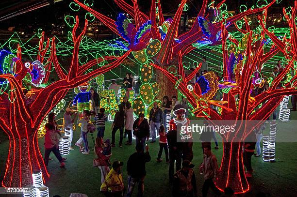 People attend the Christmas lights illumination in the Medellin river on December 1 2012 in Medellin Antioquia department Colombia AFP PHOTO/Raul...