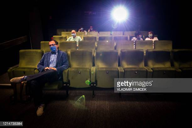 People attend the first movie screening at Lumiere cinema in Bratislava on May 22 2020 after more than two months of a lockdown caused by the novel...