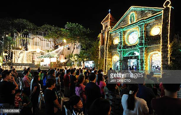 People attend the first of nine dawn masses at a Roman Catholic Church in Las Pinas City on the outskirts of Manila on December 16 2012 to signal the...