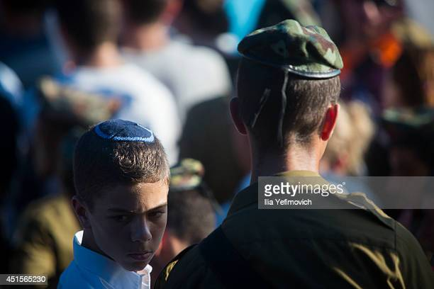 People attend the funeral ceremony held for the three Israeli teenagers found dead on July 1 2014 in Modiin Israel The bodies of Eyal Yifrah Gilad...