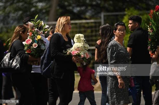 People attend the funeral of Salvadoran migrant Oscar Martinez and his almost twoyearold daughter Angie Valeria who both drowned while trying to...