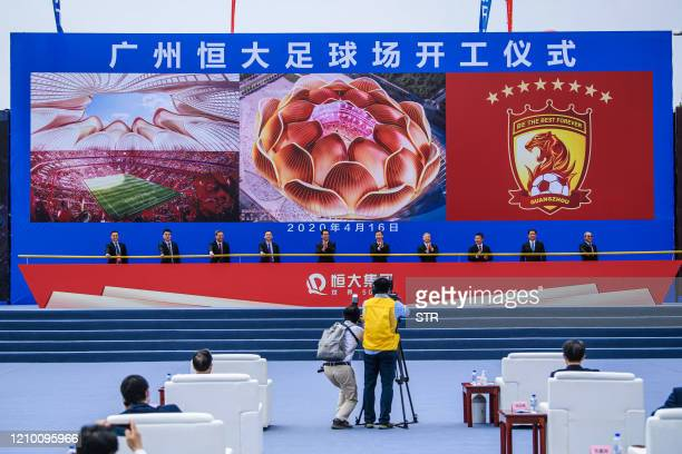 People attend the ground-breaking ceremony of Guangzhou Evergrande's new stadium in Guangzhou in China's southern Guangdong province on April 16,...