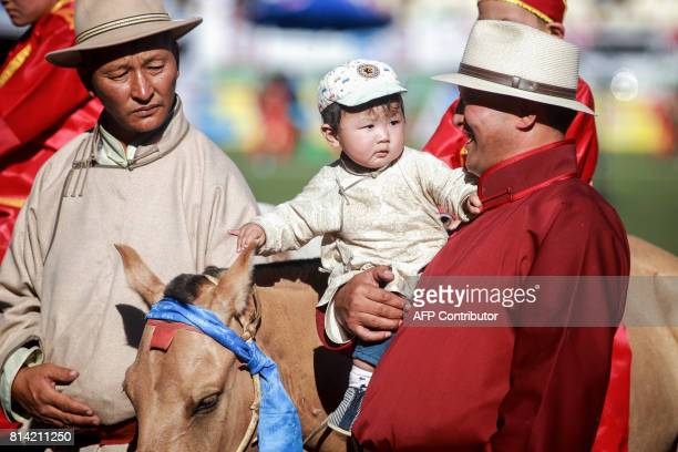 People attend the horses race of the traditional Nadaam festival in Ulan Bator on July 12 2017 The festivities consist of a number of national...