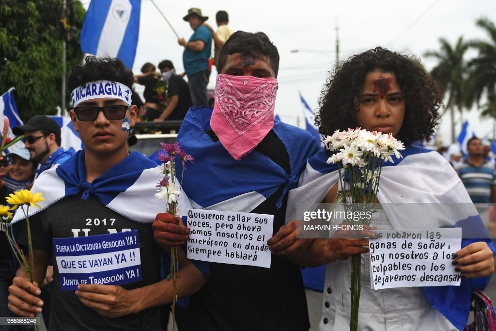 People attend the 'Marcha de las Flores' -in honor of the children killed during protests- in Managua on June 30, 2018. - At least six people were shot and wounded Saturday while protesting President Daniel Ortega in Nicaragua's capital, an AFP reporter said.