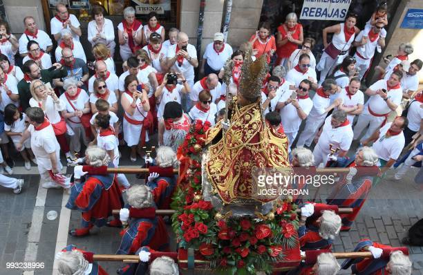 People attend the procession of Pamplona´s patron Saint Fermin on the first day of the San Fermin bull run festival in Pamplona northern Spain on...