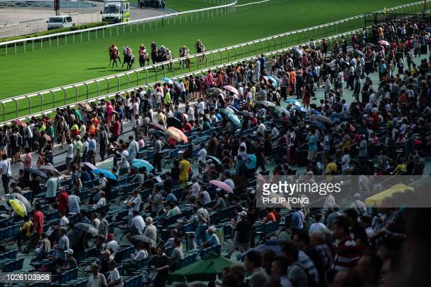 People attend the season opening horse race at the Sha Tin Racecourse of the Hong Kong Jockey Club in Hong Kong on September 2 2018