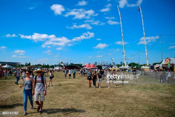 People attend the Solidays music festival on June 23, 2017 at the Longchamp Hippodrome in Paris. / AFP PHOTO / Martin BUREAU