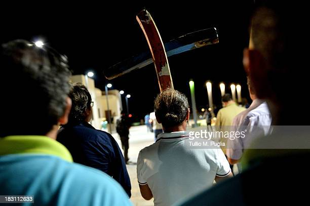 People attend the torchlight procession in memory of the victims of the immigrant boat disaster on October 4 2013 in Lampedusa Italy The search for...