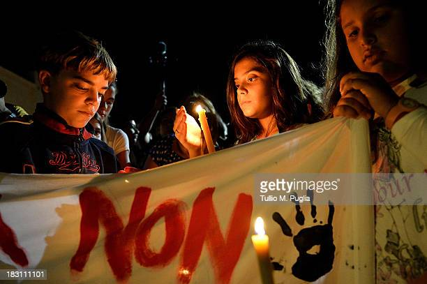 People attend the torchlight procession in memory of victims of a immigrants boat disaster on October 4 2013 in Lampedusa Italy The search for bodies...
