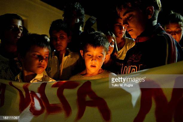 People attend the torchlight procession in memory of victims of the immigrant boat disaster on October 4 2013 in Lampedusa Italy The search for...