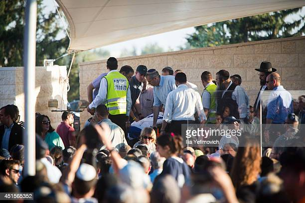 People attend to the bodies before the funeral ceremony held for the three Israeli teenagers on July 1 2014 in Modiin Israel The bodies of Eyal...