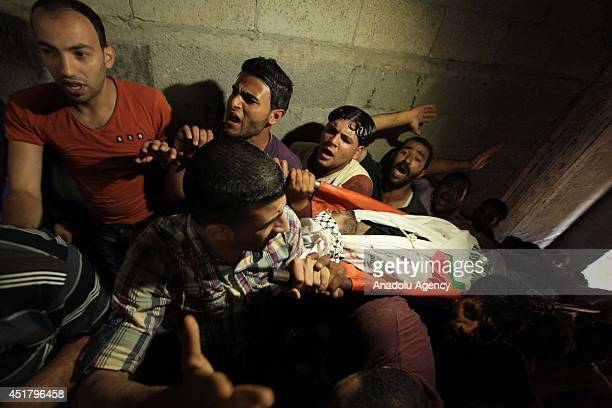 People attending funeral carry the body of Palestinian Marwan Sleem during his funeral in the central Gaza Strip Gaza on July 7 2014 Israeli...