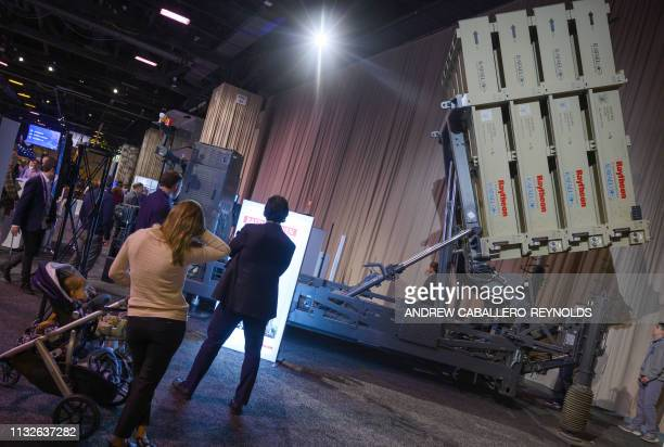 People attending the American Israel Public Affairs Committee conference walk past an Iron Dome defense missile system on display in Washington, DC...