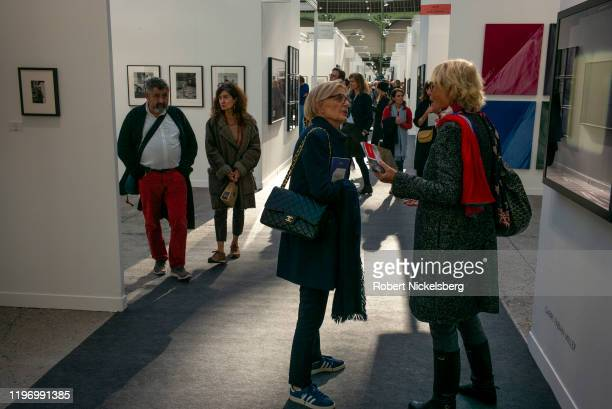 People attending the annual Paris Photo photography art fair meet in a hallway of photographs at the Grand Palais in Paris, France on November 6,...