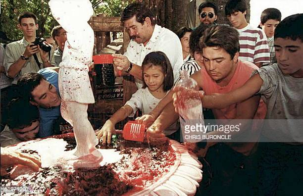 People attending the ninth Curico grape harvest festival fill up containers with first pressing during the celebrations for the new harvesting season...