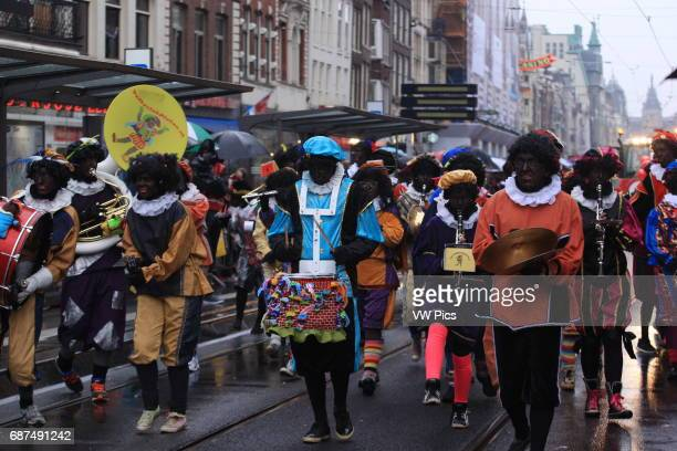 People attends the arrival of Sinterklaas the Dutch version of Santa Claus and his 'Zwarte Piet' or Black Pete with blackface in Amsterdam...