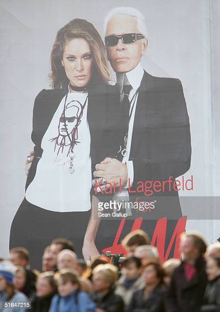 People await the arrival of British Queen Elizabeth II near a giant 1500 square meter advertisement for Swedish fashion retailer HM that shows...
