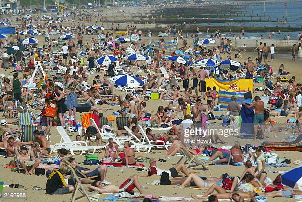 People bask in the sun on Bournemouth beach on July 15 2003 in Bournemouth England UK temperatures were expected to hit 31C