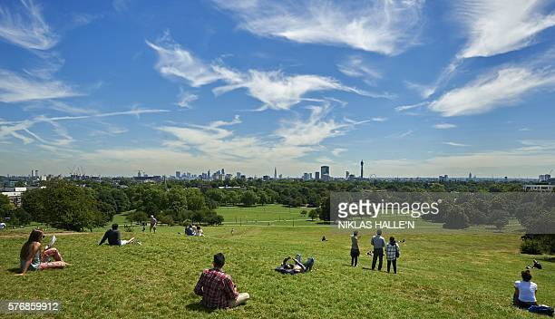 People bask in the sun on Primrose Hill north London on July 18 backdropped by a view of the City of London skyline The majority of the country was...