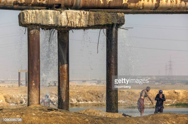 People bath as water falls from a water pipe leakage in Karachi Pakistan on Monday Dec 24 2018 Women and children walk miles each day in search...