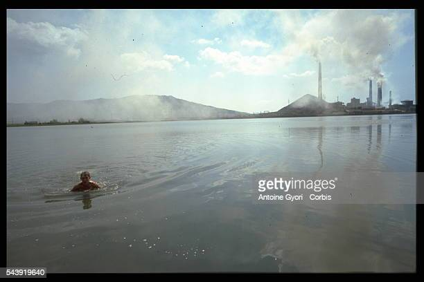 People bathe in the lake opposite the Karabachmed copper foundry