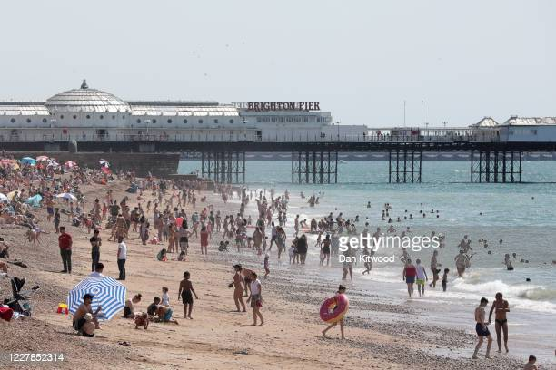 People bathe in the sea near Brighton pier during a heatwave on July 31, 2020 in Brighton, England.