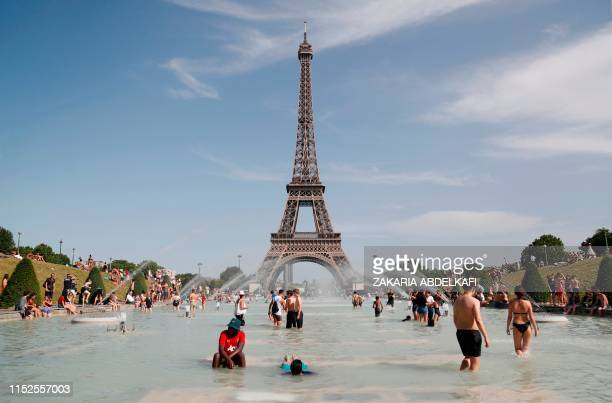 People bathe in the Trocadero Fountain in front of the Eiffel Tower in Paris during a heatwave on June 28 2019 The temperature in France on June 28...